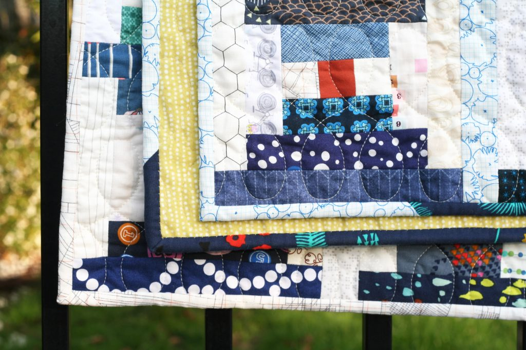 Close up of Scrappy Courthouse Steps quilt in blue and white by Wooden Spoon Quilts