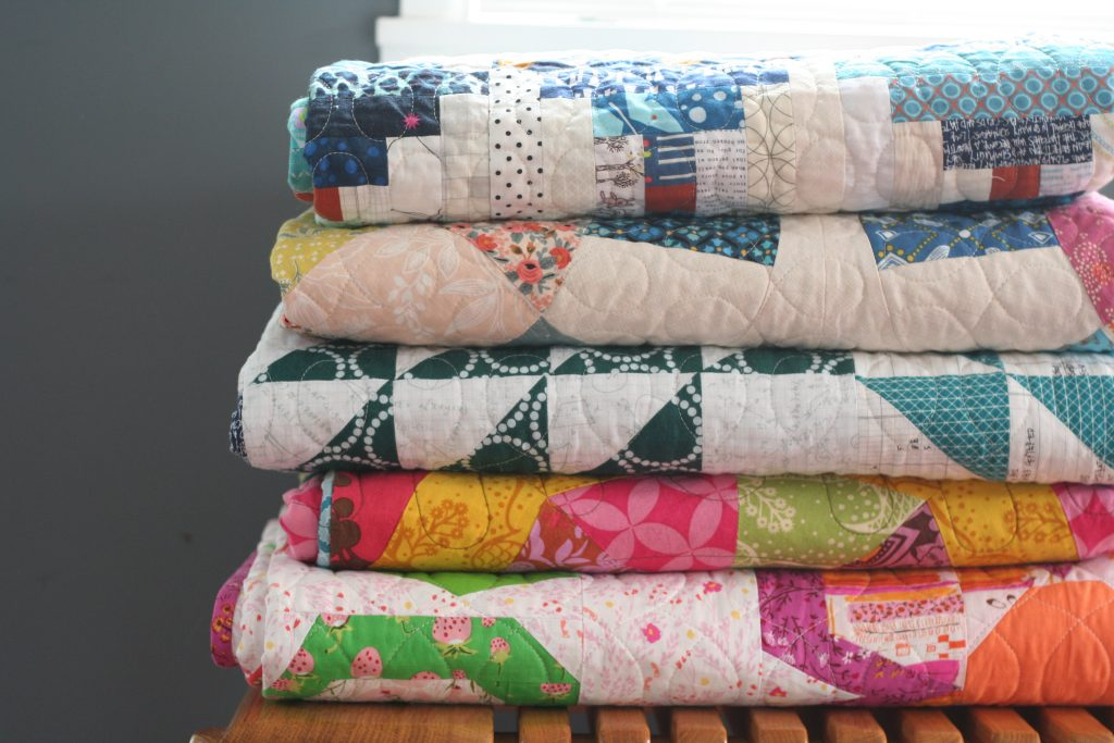 Pile of quilts by Wooden Spoon Quilts