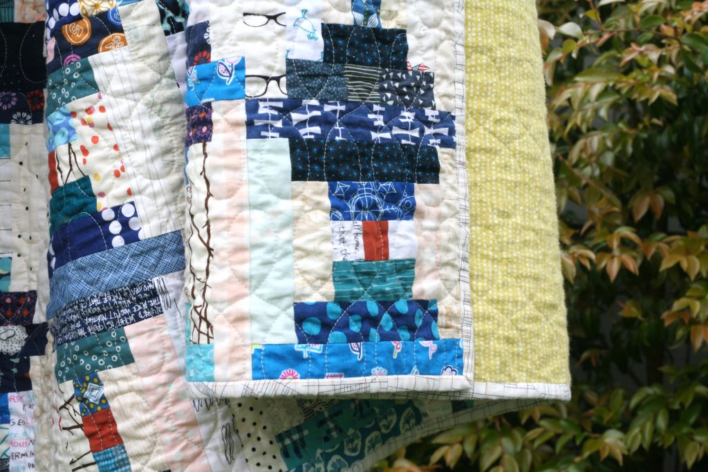 Closeup of blue and white scrappy courthouse steps quilt by Wooden Spoon Quilts